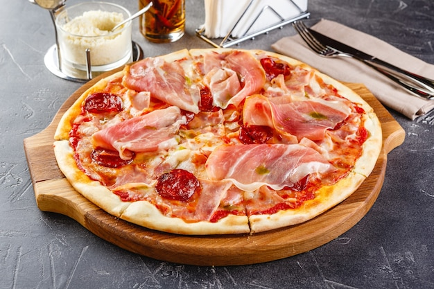 Pizza mit salami und schinken auf holzbrett