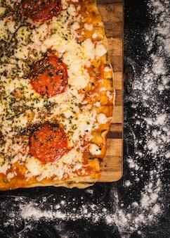 Pizza mit schach und tomaten auf einer schwarzen oberfläche