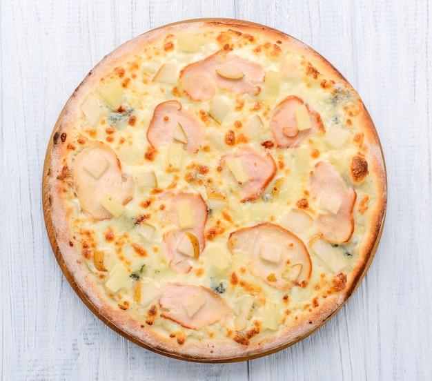 Pizza mit schinken, äpfeln und ananas