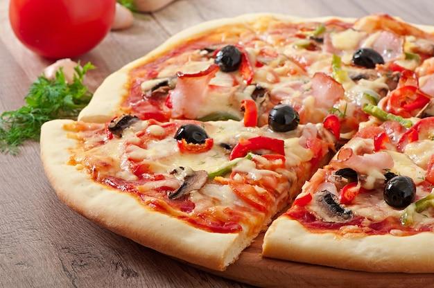 Pizza mit schinken, champignons und oliven