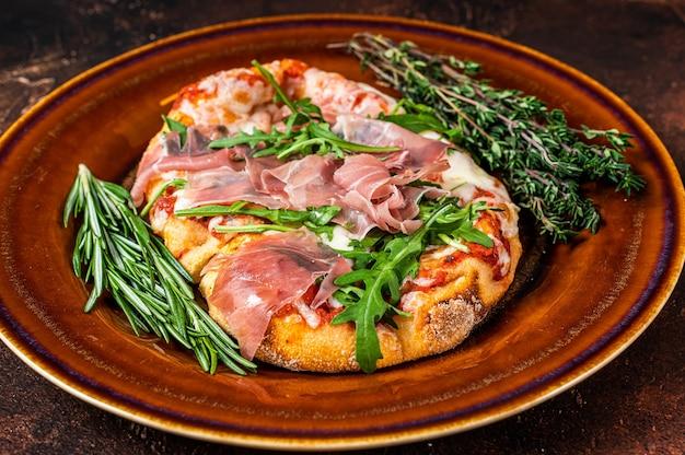 Pizza mit schinken-parmaschinken, rucola-salat und parmesan in einem rustikalen teller