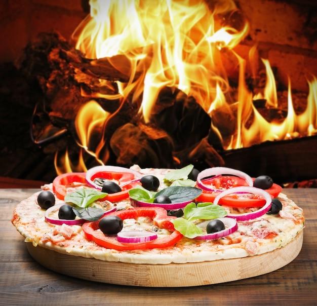 Pizza mit schinken und käse auf dem feuer gekocht