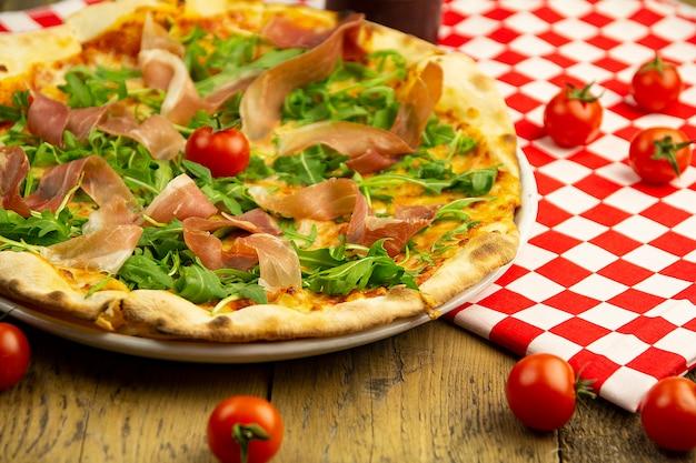 Pizza mit schinken und rucola auf einem holztisch