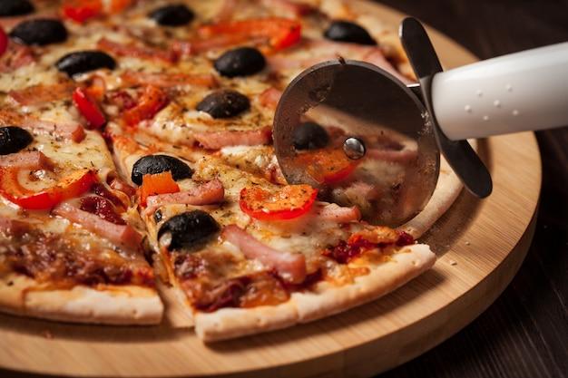 Pizza mit schinken und schwarzen oliven schneiden
