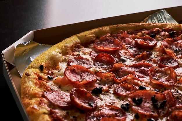 Pizza mit speck in einer pappschachtel auf einem dunklen hintergrund. nahansicht. von oben betrachten. pizzalieferdienst