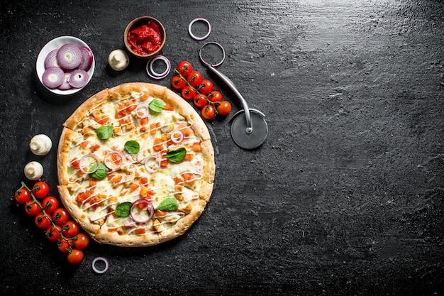 Pizza mit tomaten auf einem zweig auf schwarzem rustikalem tisch