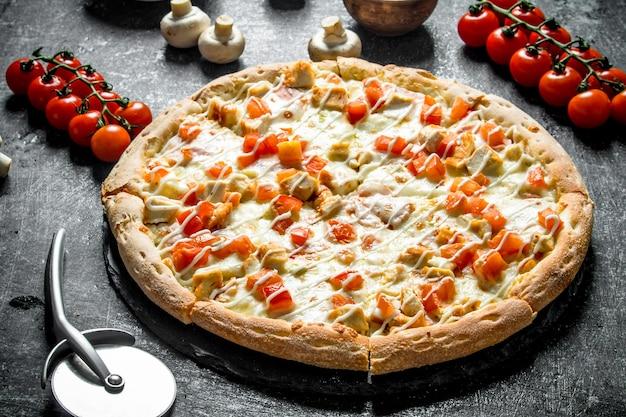 Pizza mit tomaten, huhn und käse auf dunklem holztisch