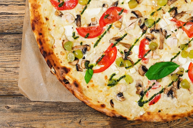 Pizza mit tomaten, mozzarella, pilzen und basilikum pesto. pizza