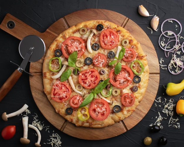Pizza mit tomaten, oliven und pilzen. italienische küche. zutaten für die herstellung von pizza