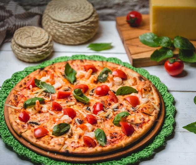 Pizza mit tomaten und basilikum auf dem tisch