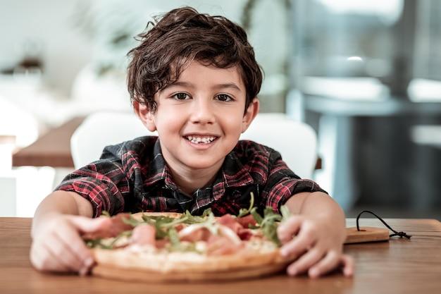 Pizza mit vater. netter dunkelhaariger sohn, der aufgeregt ist, pizza mit seinem bärtigen fürsorglichen vater zu essen
