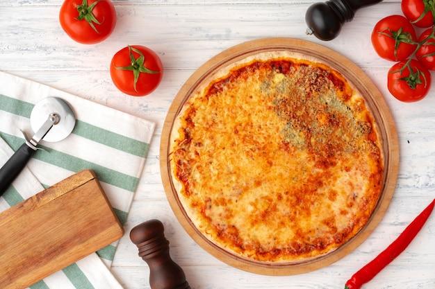 Pizza mit vier käsesorten serviert auf draufsicht des hölzernen hintergrunds