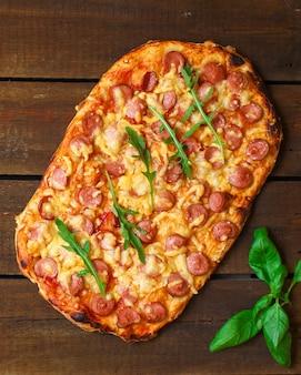 Pizza mit würstchen (tomatensauce, käse, fleisch)