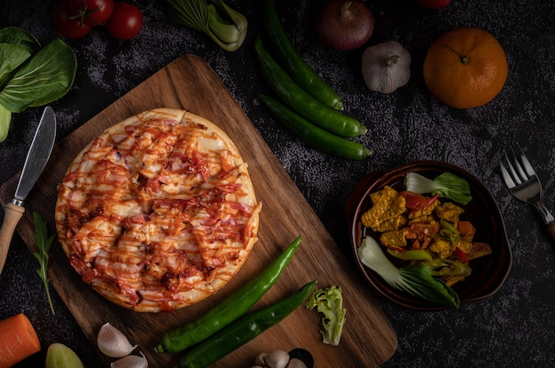 Pizza mit wurst, mais, bohnen, garnelen und speck auf einem holzteller