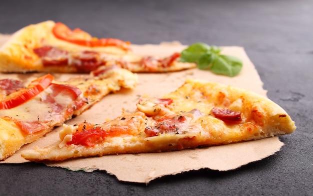 Pizza mit wurst, schinken, tomaten und käse, mit basilikum dekoriert und auf pergament in stücke geschnitten