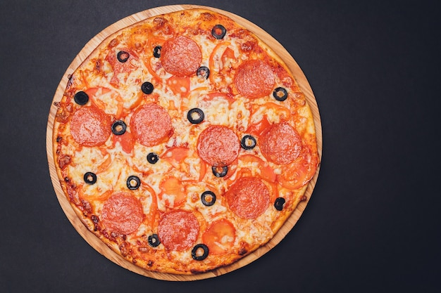 Pizza peperoni, mozzarella, oregano auf einem schwarzen hintergrund.