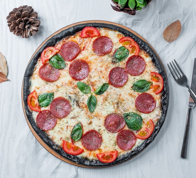 Pizza pepperoni mit tomaten basilikum und käse