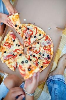 Pizza teilen, hände nehmen ein stück pizza aus einer kiste im freien,
