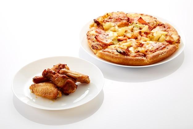 Pizza und gebratene hühner sind weiße teller