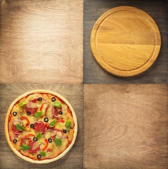 Pizza und schneidebrett am holztisch, ansicht von oben