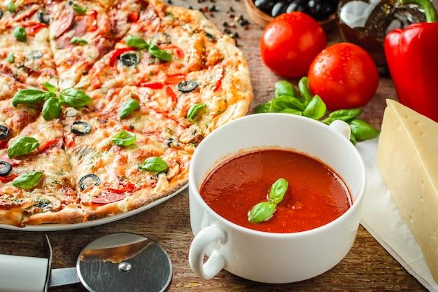 Pizza und zutaten auf einem hölzernen hintergrund.
