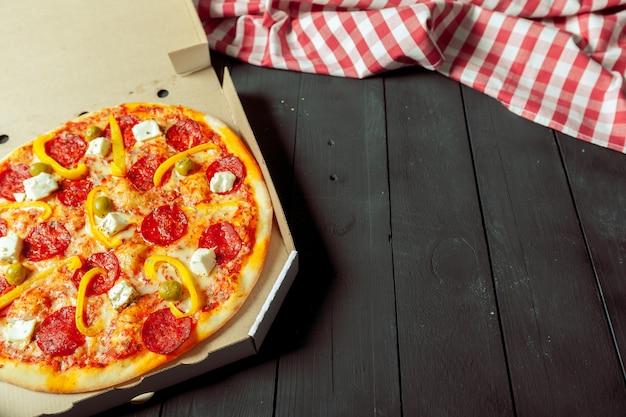 Pizza wird in der schachtel auf dem tisch neben dem stoff geliefert