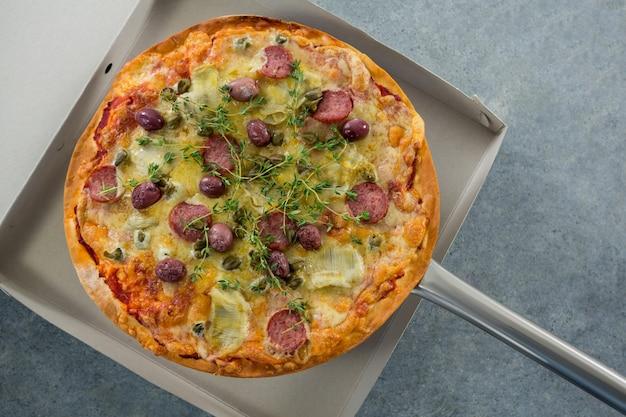 Pizza wird in eine schachtel gelegt