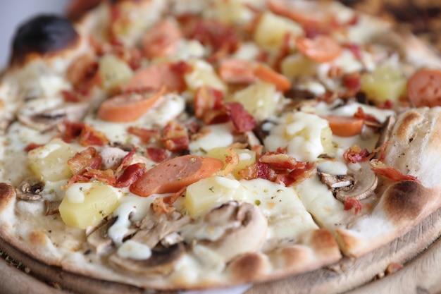 Pizza wurst speck und ananas auf holz, pizza hawaii