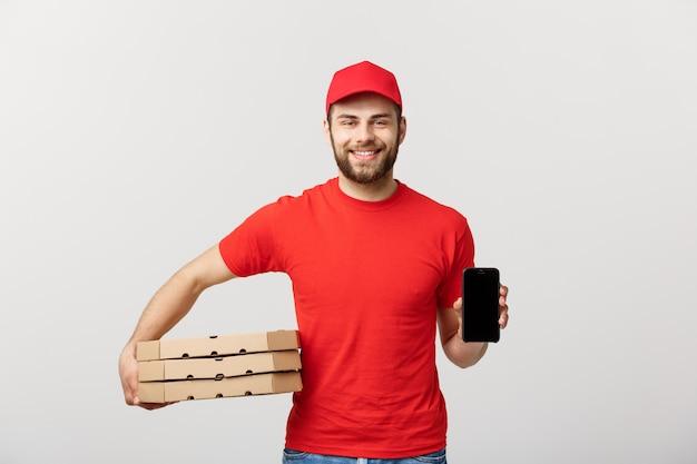 Pizzabote, der ein mobile und pizzakästen über weißem hintergrund hält.