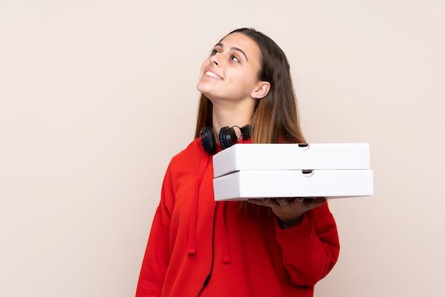 Pizzabote, der eine pizza über der lokalisierten wand oben schaut beim lächeln hält