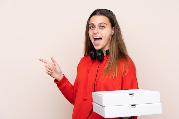 Pizzabote, der eine pizza über lokalisierter wand überrascht hält und finger auf die seite zeigt