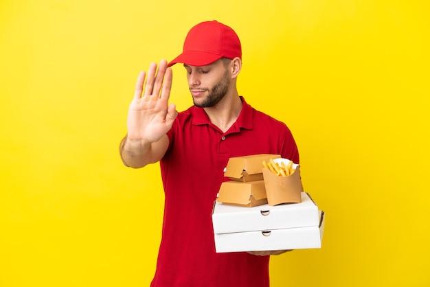 Pizzabote, der pizzakartons und burger über isoliertem hintergrund abholt, stop-geste macht und enttäuscht