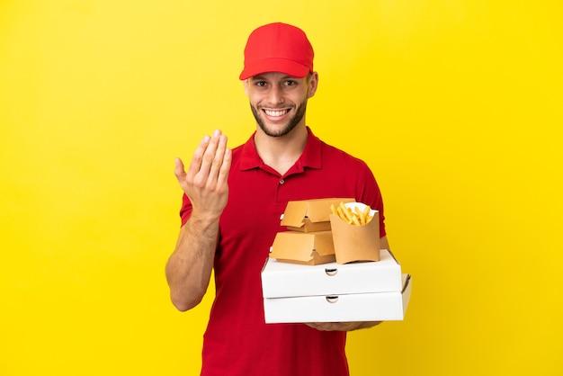 Pizzabote, der pizzakartons und burger über isoliertem hintergrund abholt und einlädt, mit der hand zu kommen. schön, dass du gekommen bist