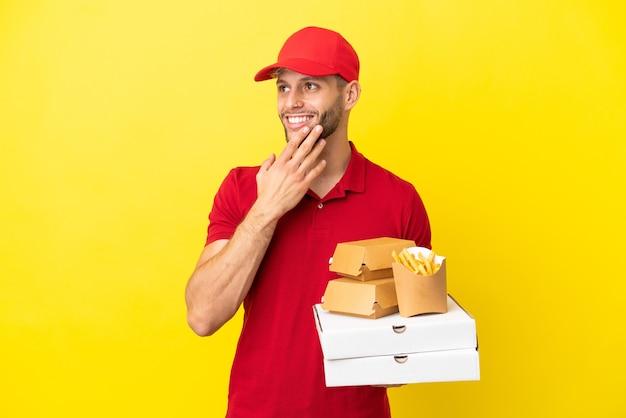 Pizzabote, der pizzakartons und burger über isoliertem hintergrund abholt und lächelnd nach oben schaut