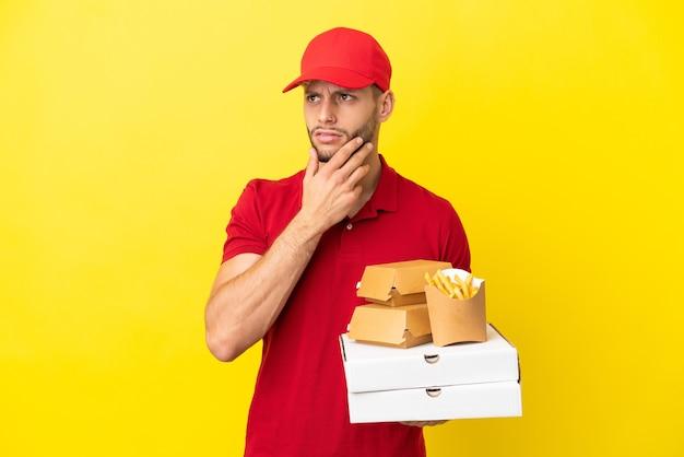 Pizzabote, der pizzakartons und burger über isoliertem hintergrund abholt und zweifel hat
