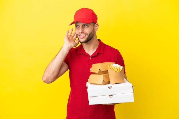 Pizzabote, der pizzakartons und burger über isoliertem hintergrund aufhebt und etwas hört, indem er die hand auf das ohr legt