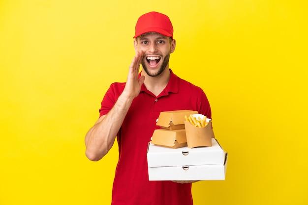 Pizzabote, der pizzakartons und burger über isoliertem hintergrund mit überraschung und schockiertem gesichtsausdruck abholt