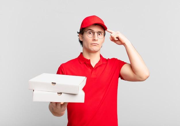 Pizzabote, junge, der sich verwirrt und verwirrt fühlt und zeigt, dass sie verrückt, verrückt oder verrückt sind