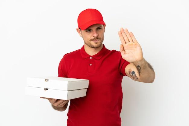 Pizzabote mit arbeitsuniform, der pizzakartons über isolierter weißer wand aufhebt, die stoppgeste macht und enttäuscht