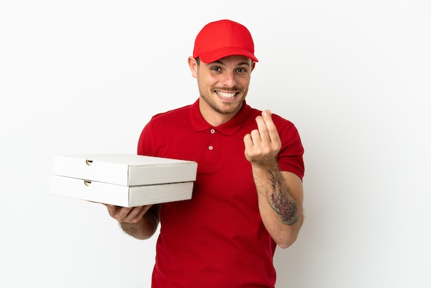 Pizzabote mit arbeitsuniform, der pizzakartons über isolierter weißer wand aufhebt und geldgeste macht