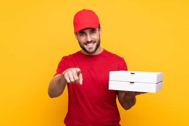 Pizzabote mit der arbeitskleidung, die pizzakästen über lokalisierter gelber wand aufhebt, zeigt finger auf sie mit einem überzeugten ausdruck
