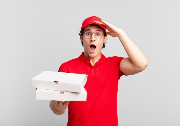 Pizzabote sieht glücklich, erstaunt und überrascht aus, lächelt und erkennt erstaunliche und unglaublich gute nachrichten