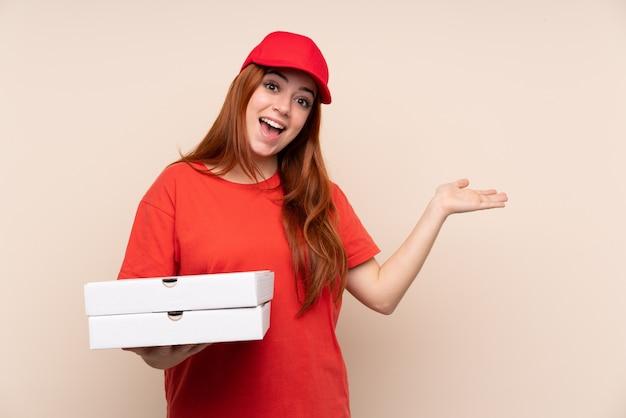 Pizzaboten-teenager-mädchen, das eine pizza hält, die hände zur seite ausstreckt, um einzuladen, zu kommen