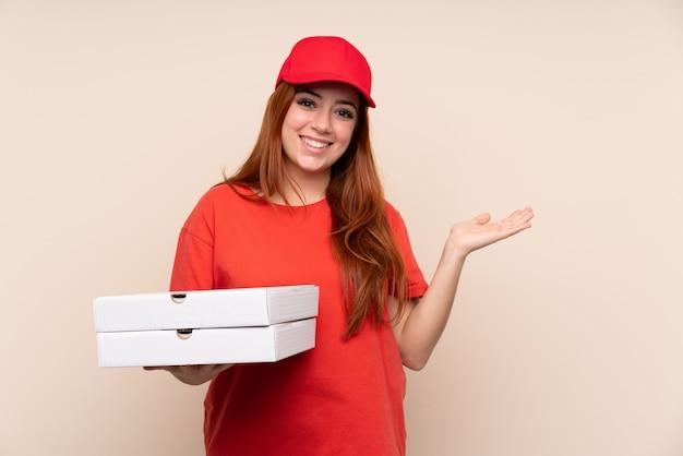 Pizzaboten-teenager-mädchen, das eine pizza hält, die imaginären copyspace auf der handfläche hält