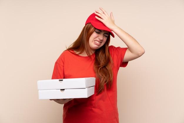 Pizzaboten-teenager-mädchen, das eine pizza hält, die zweifel mit verwirrendem gesichtsausdruck hat