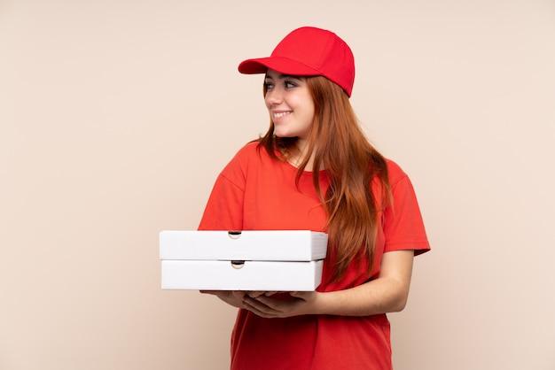 Pizzaboten-teenager-mädchen, das eine pizza über isolierter wand hält, die zur seite schaut