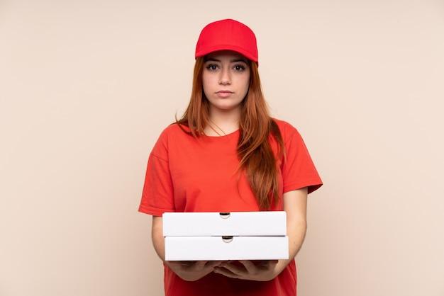 Pizzaboten-teenagerfrau, die eine pizza über isolierter wand hält, die arme verschränkt hält