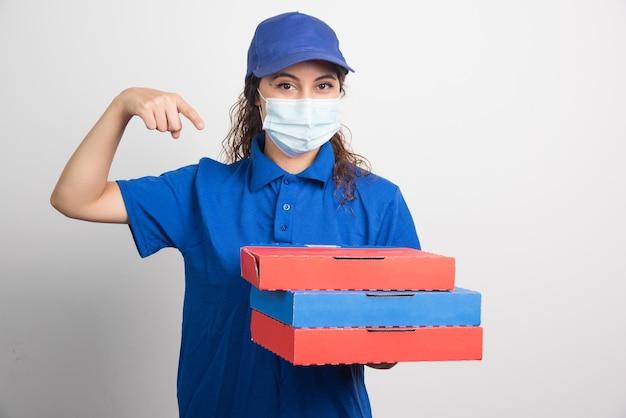 Pizzalieferant, der drei kisten mit medizinischer gesichtsmaske auf weiß hält