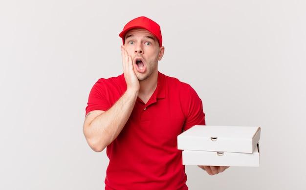 Pizzalieferant, der sich schockiert und verängstigt fühlt und mit offenem mund und händen auf den wangen verängstigt aussieht