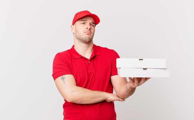 Pizzalieferant zuckt mit den schultern, fühlt sich verwirrt und unsicher, zweifelt mit verschränkten armen und verwirrtem blick